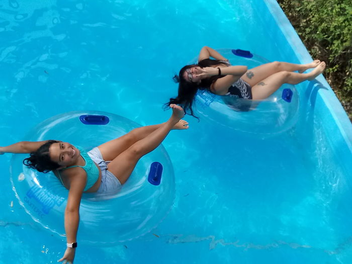 Full length of young woman lying in swimming pool