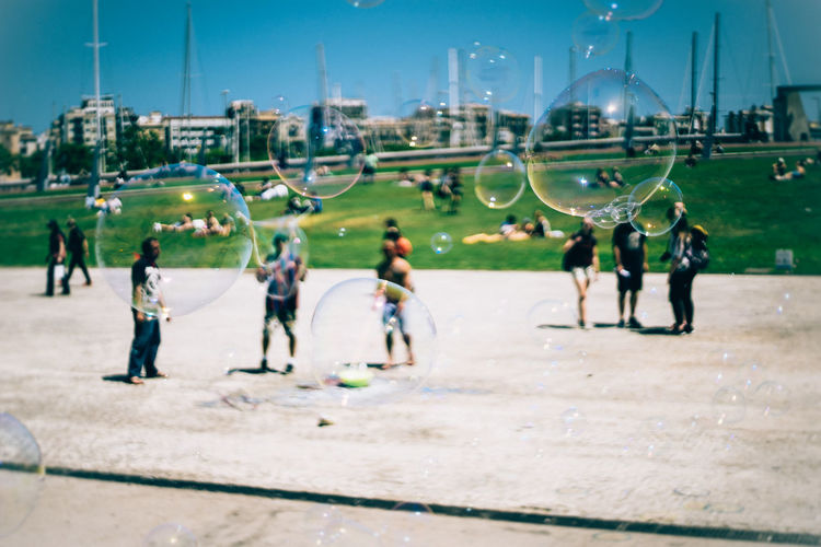 Bubbles Soap Bubble Outdoors Dreamy Dreamy Days When It Is Sunny Sunny Day 🌞 Sunny Chill Daydreaming Bubble In The Air Bubbles Rainbow Barcelona Real People Day Sky People City Men Outdoors The Graphic City Adventures In The City