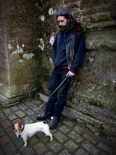 Full Length Of Man With Dog Standing Against Wall