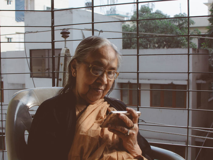 Senior woman looking at phone while sitting in balcony