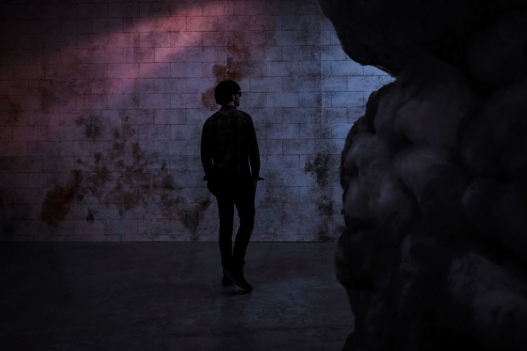 Rear view of silhouette man standing in corridor