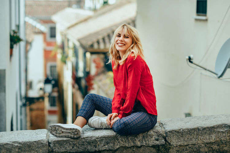 Portrait of cheerful young woman sitting on retaining wall in town