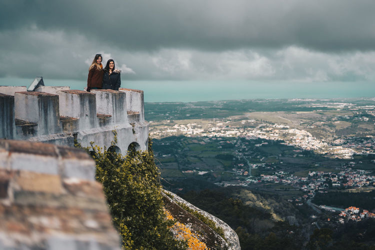 Friends standing on castle against cloudy sky