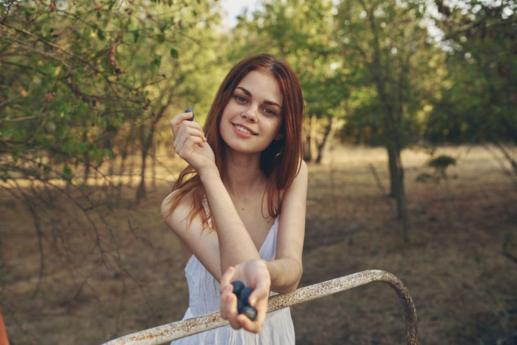 Portrait of smiling young woman holding plant against trees