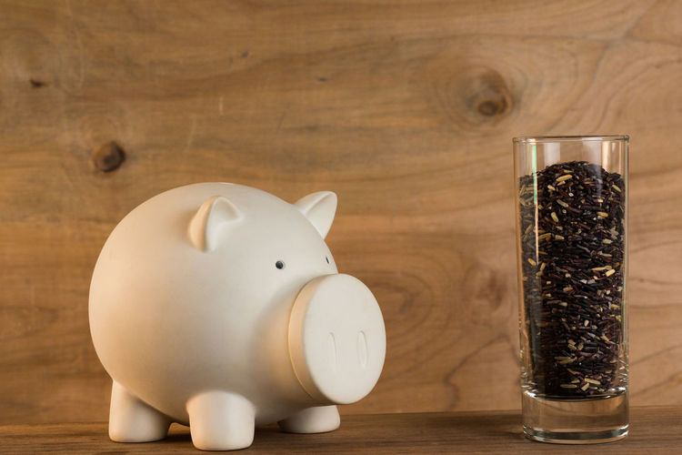 Close-Up Of Piggy Bank And Food In Glass On Table
