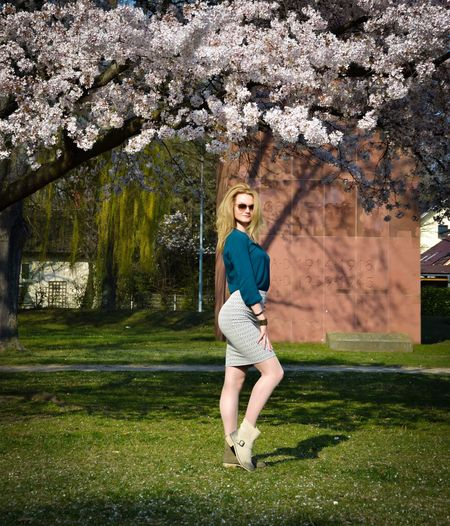 Full length portrait of woman standing on grass by cherry tree