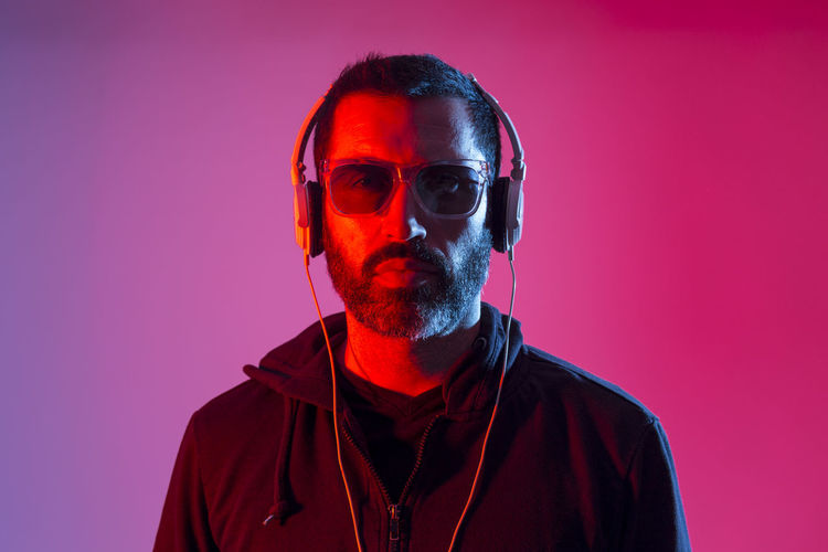 Portrait of man wearing sunglasses against red background