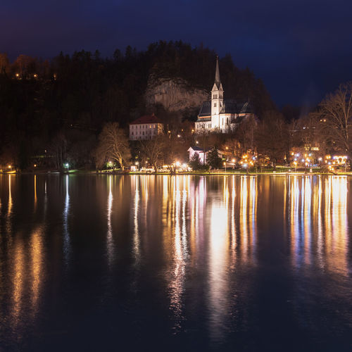 Night on lake bled. christmas atmosphere and lights. castle and church of the annunciation
