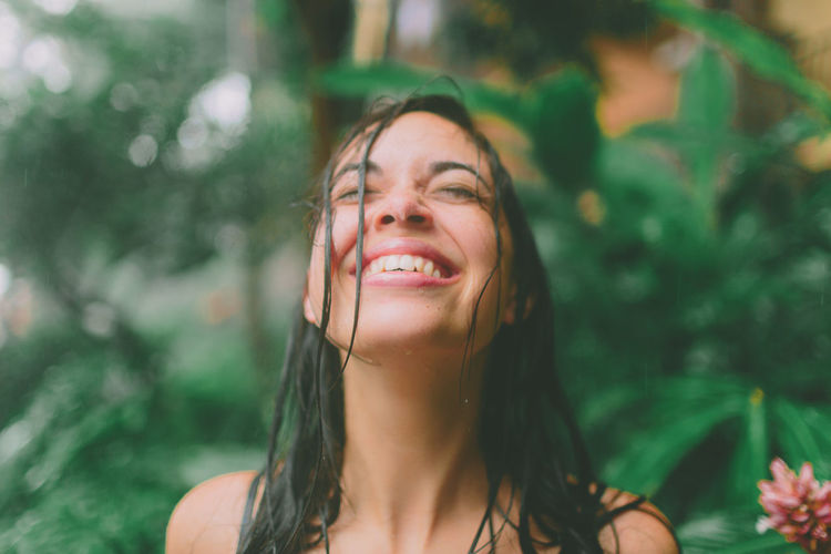 A young woman looking up to the sky as the rain falls. EyeEmNewHere Free Happy Rain Beautiful Woman Beauty Close-up Day Focus On Foreground Happiness Headshot Leisure Activity Lifestyles Looking At Camera Nature One Person Outdoors People Portrait Real People Smiling Young Adult Young Women