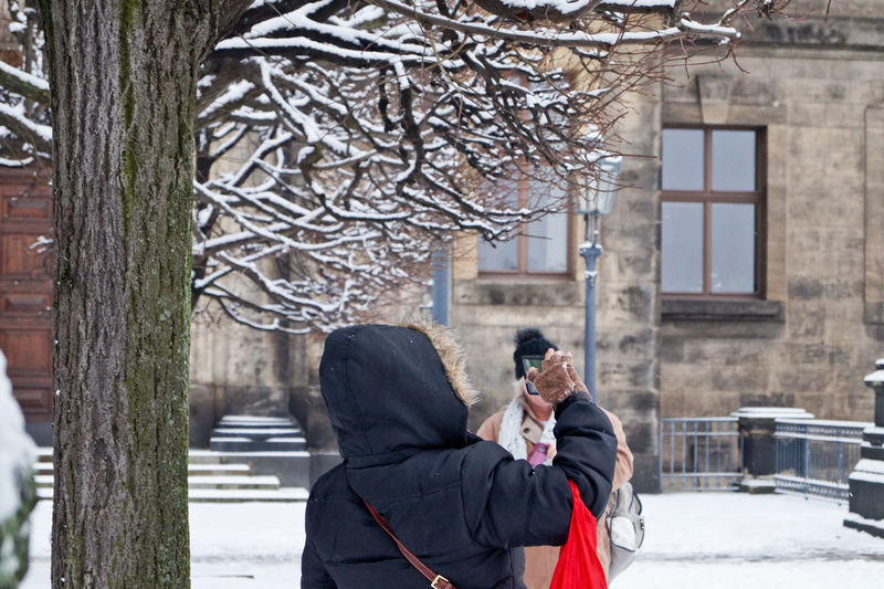 Rear View Of Person Taking Selfie While Standing By Tree During Winter
