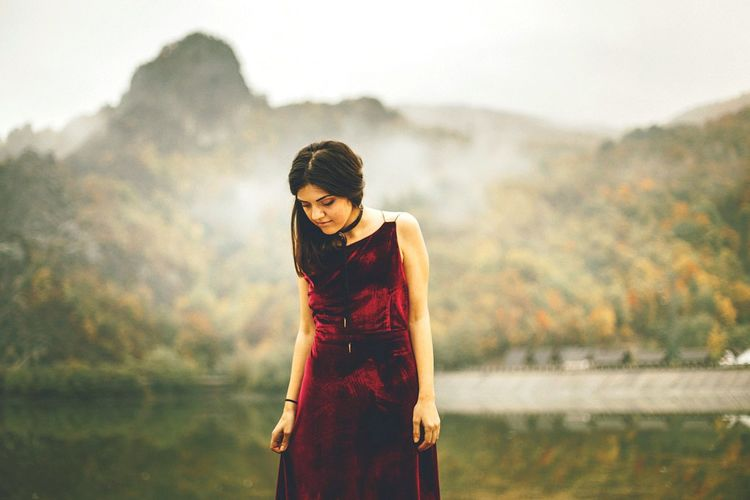 Portrait Of Woman In Red Dress Against Mountain