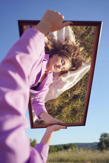 Portrait of woman holding plant against sky