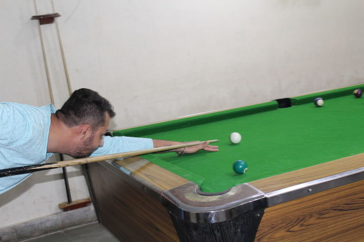 Side view of man playing snooker in room