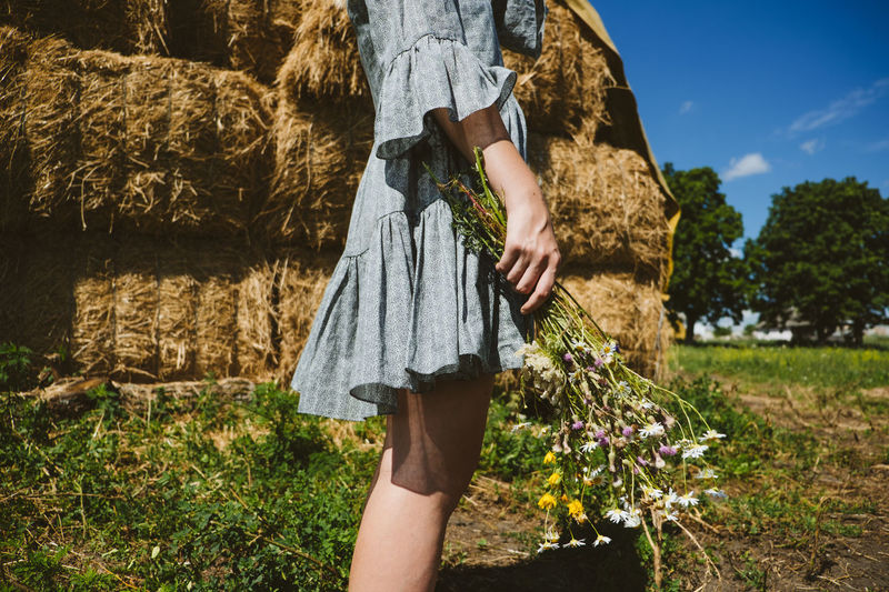 Young girl in rubber boots with flowers standing against the background of straw bales on country