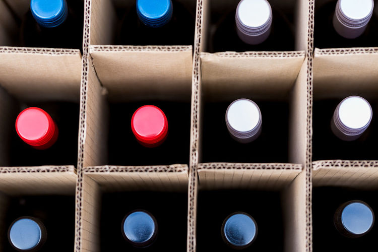Top view on wine bottles in cardboard case Cardboard Box Drinks With Friends Index Share Food Wines Alcoholism Black Background Cardboard Case Case Of Wine Close-up Dots Edges And Corners Export For Sale Full Frame Investment Large Group Of Objects Metal Caps Mixed Case Points Round Stock Top View Top View Of Food Wealth