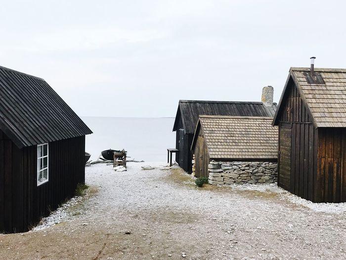 Huts on beach against clear sky