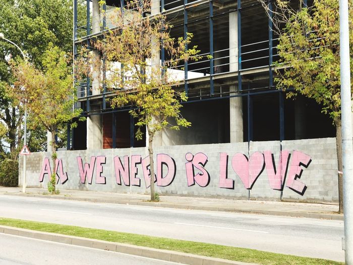 All we need is Love Words All We Need Is Love All You Need Is Love Love Built Structure Building Exterior Plant Architecture Tree Text Communication Street Window Sign Western Script Outdoors Building Road City Day Graffiti No People
