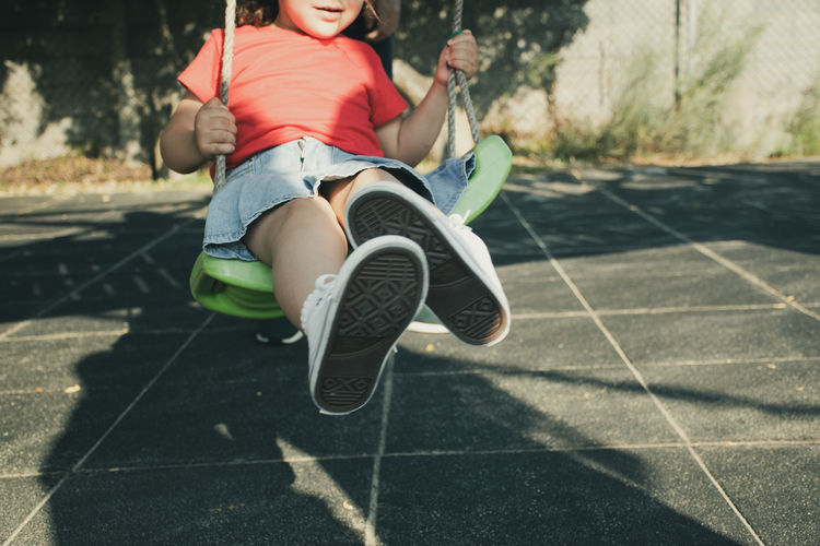Low section of girl on swing at park