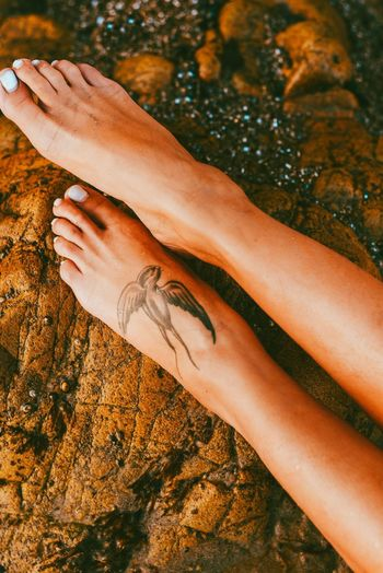 Low section of woman with tattoo on rock