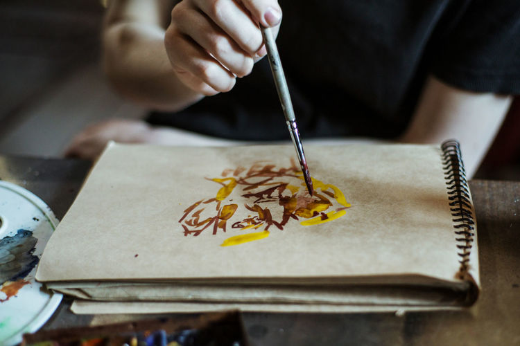 Holding Brush One Person Paintbrush Art And Craft Indoors  Creativity Table Paper Selective Focus Hand Human Body Part Skill  Real People Human Hand Art ArtWork Artist Paint Painting Watercolor Painting Watercolor Midsection Watercolor Paints