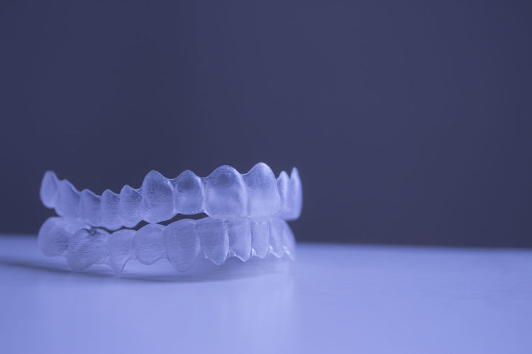 Close-up of plastic dentures on table against gray background
