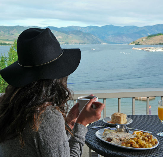 Close-up of woman in hat holding coffee cup against lake chelan