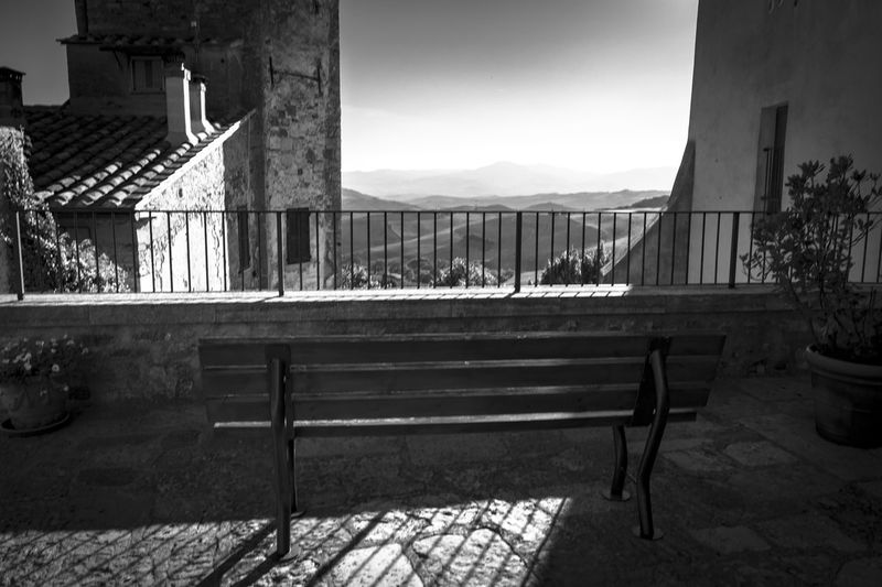 Empty benches and table by buildings against sky