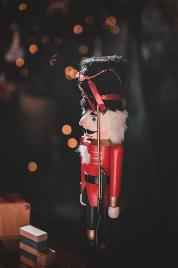 Soldier figurine and toy blocks on table against defocused lights