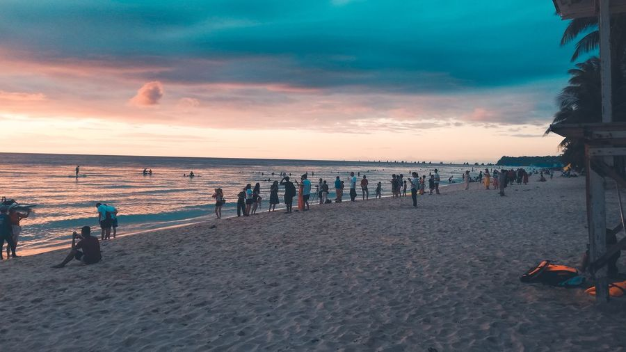Group of people on beach against sky during sunset