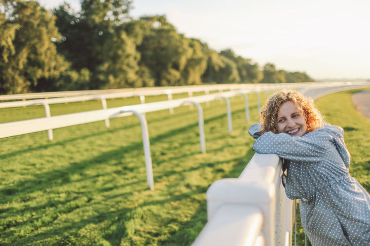 Smiling young woman leaning on fence