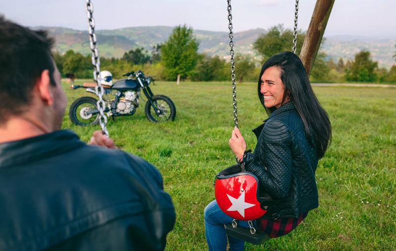 Rear view of smiling woman on swing in field
