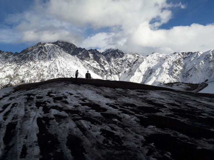 Woman standing by cross against snowcapped mountains