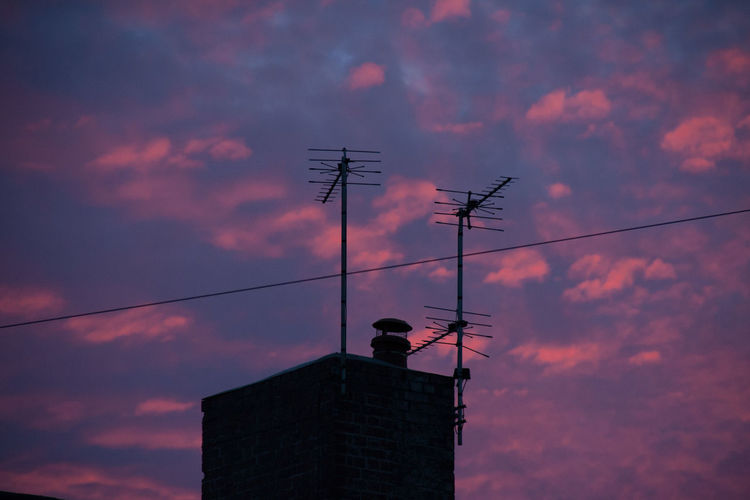 Low angle view of antennas on building at sunset