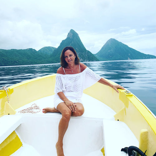 Young woman sitting on boat against pitons