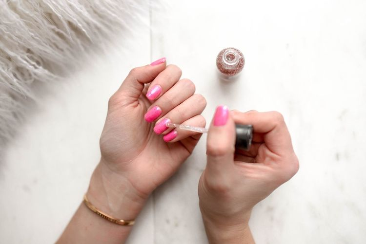 Cropped hands of woman applying pink nail polish on table