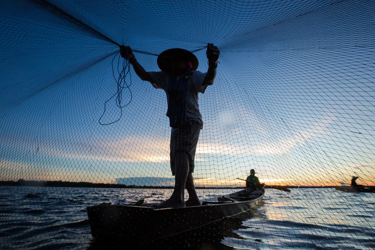 Man With Fishing Net During Sunset