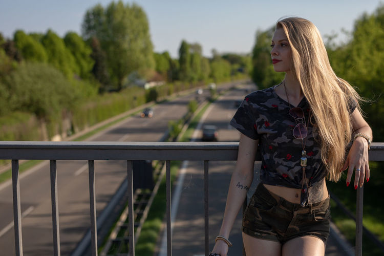 Young Woman Looking Away While Standing By Railing On Footbridge