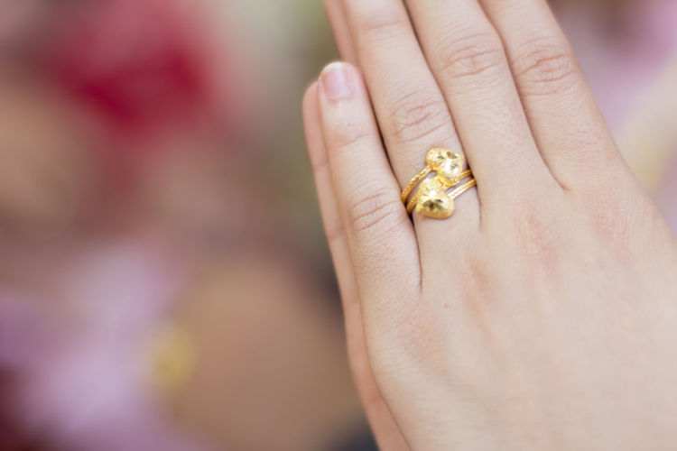 Close-up of woman hand wearing golden ring