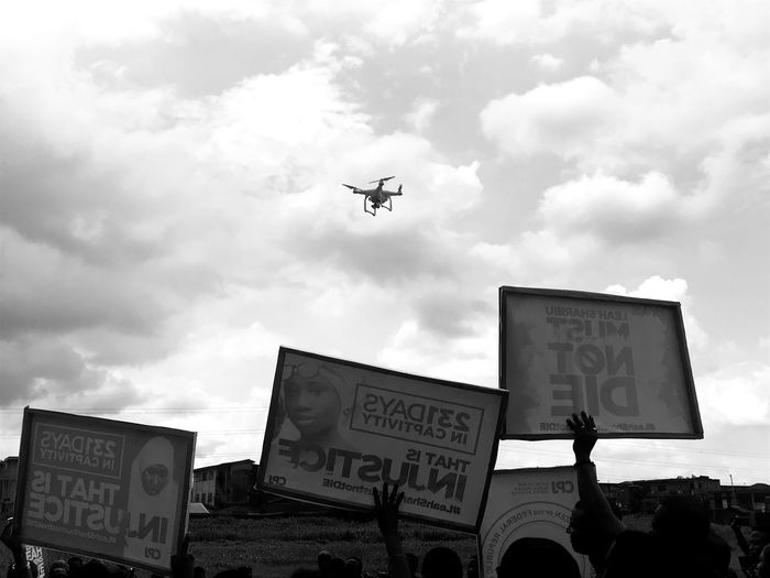 Protest and Drone Protest TheWeekOnEyeEM Sky Cloud - Sky Communication Low Angle View Sign Architecture Nature Mid-air Built Structure Transportation City Mode Of Transportation No People Basketball Hoop Day Outdoors Text Flying Building Exterior
