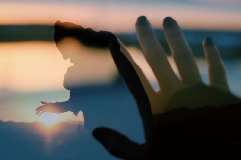 Sunset Human Hand Sky Nature Real People One Person Silhouette Focus On Foreground Water Hand Reflection Sunlight Human Body Part Close-up Orange Color Lifestyles Leisure Activity Human Finger Finger Arms Raised