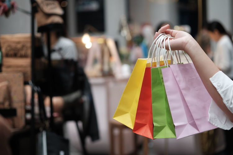 Cropped hand of woman holding shopping bags