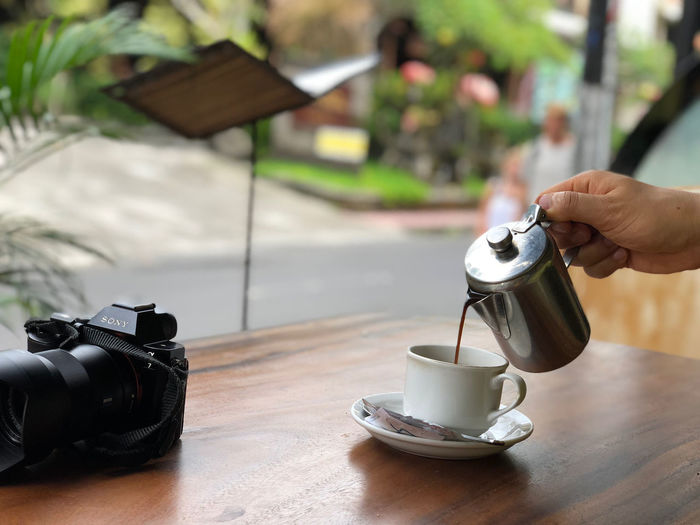 Bali Travel Activity Body Part Camera - Photographic Equipment Coffee Coffee - Drink Coffee Cup Crockery Cup Digital Camera Drink Food Food And Drink Hand Holding Hot Drink Human Body Part Human Hand Mug One Person Photography Themes Real People Table Ubud
