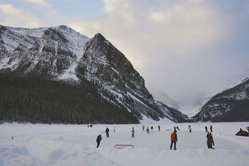 People Skiing On Frozen Lake Louise In Front Of Mountains Against Cloudy Sky