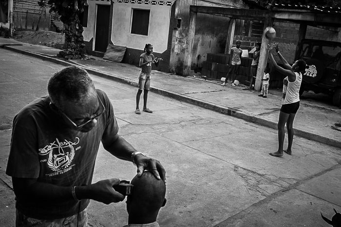 A man who cuts hair in the street and kids playing in the background. Barbershop Black And White Games Kids Play Playground Poverty Street Photography Venezuela First Eyeem Photo