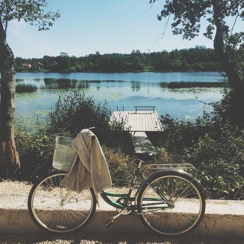 Bicycle by lake against sky