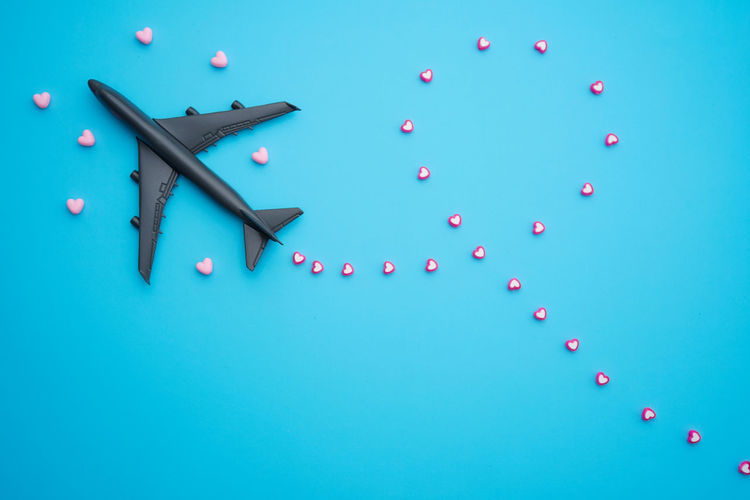 Travel valentine day concept flat lay design with airplane and heart shape beads on blue background