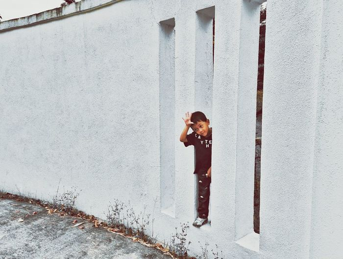 Playful Little Boy Standing Amidst Walls