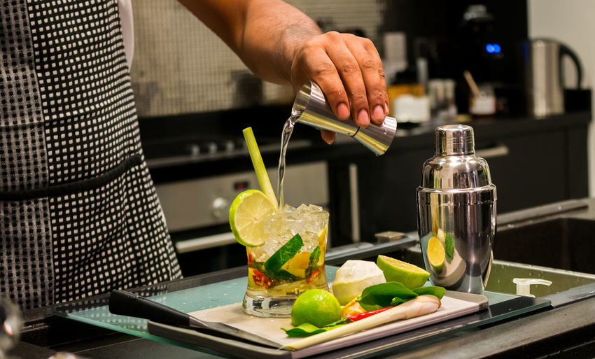 Midsection Of Bartender Preparing Cocktail