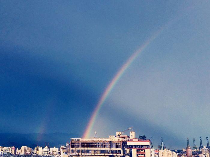 Rainbow over city against blue sky
