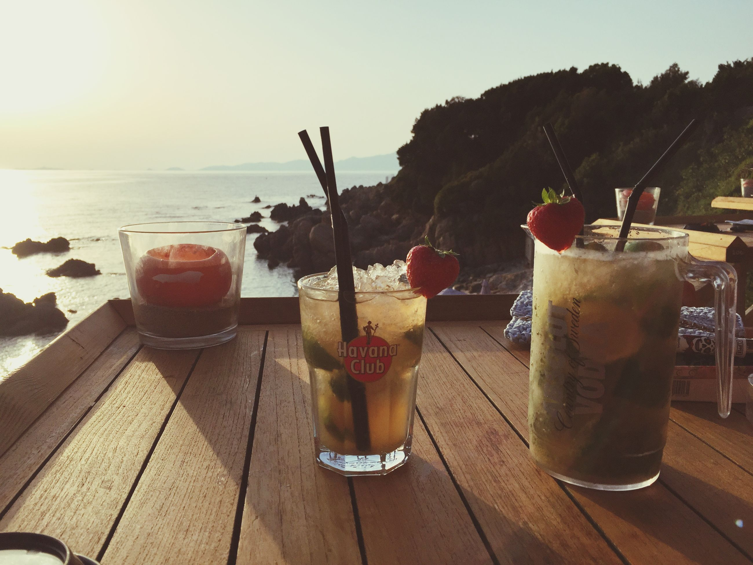 drink, table, freshness, food and drink, refreshment, drinking glass, flower, close-up, still life, drinking straw, focus on foreground, water, potted plant, sunlight, indoors, sea, restaurant, alcohol, vase, beauty in nature